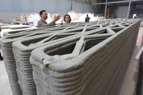Ma Yihe (left) shows the 3D-printed walls for houses his company is building in Shanghai, China. His company plans to build 10 of these in a day.