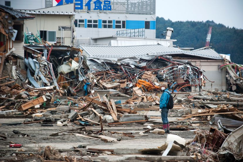 A person surveys the devastating aftermath of the 2011 earthquake and tsunami in Japan.  © Paul Taggart/Corbis