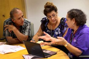 Affordable Care Act navigator Nini Hadwen (R) speaks with Jorge Hernandez (L) and Marta Aguirre as they shop for health insurance during a navigation session put on by the Epilepsy Foundation Florida.