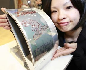 A Fujitsu employee displays the prototype model of an electronic paper display that is flexible and does not blur even if it is bent or pressed by a finger.