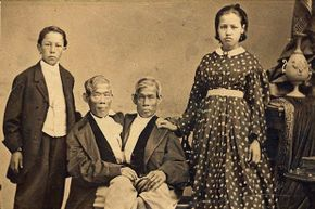 """Chang and Eng Bunker, the namesake of the phrase """"Siamese twins,"""" pose with their children."""
