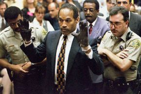 O.J. Simpson tries on the gloves found at the crime scene and his home before the jury and the court on June 15, 1995.