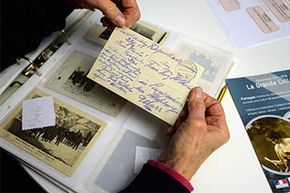 A woman holds a postcard from a family member written during World War I, part of a collection of items initiated by the French National Archives. Most countries have national archives which you can peruse for information on long-lost relatives.