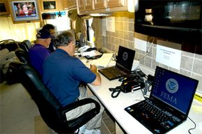 Three FEMA specialists work out of a mobile command center set up at the St. Tammany Parish Emergency Operations Center to assist those affected by Hurricane Katrina.