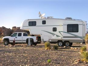 If the fifth wheel hitch is properly installed in the bed of the pickup, the weight of the trailer will press down between the cab of the truck and the rear axle.