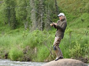 Fishing reports help people decide where to cast their lines. This woman has chosen to set up shop in an Alaskan stream.
