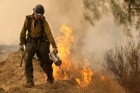 A U.S. Forest Service hotshot uses a drip torch to light a backfire. A drip torch dribbles and ignites fuel (usually either diesel or stove oil) at the pull of a trigger.