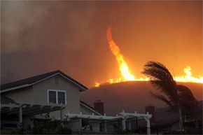 A fire tornado veers close to homes during the Freeway Complex fire on Nov. 15, 2008, in Yorba Linda, Calif. Strong Santa Ana winds helped the fire to destroy more than 30,000 acres and 314 residences.