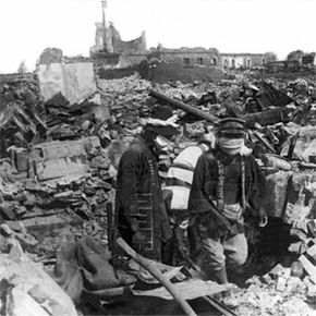 Survivors search the ruins from the devastating 1923 Yokohama earthquake and fire. There's a victim wrapped in white between the searchers.