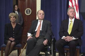 James Brady (C) who was permanently paralyzed during John Hinckley Jr.'s attempt to assassinate Ronald Reagan, sits with wife Sarah and then-President Bill Clinton on the seventh anniversary of the Brady bill in 2000.