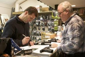 Brian O'Connor (L) of Newtown, Conn. fills out paperwork to purchase a Glock 10mm pistol at Chris' Indoor Shooting Range in Guilford, Conn. See more firearms pictures.