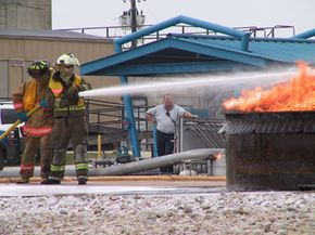 Trainees practice operating a fire hose and put out a small fire on training grounds.
