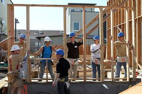 Habitat for Humanity volunteers set a wall frame as they help build a home in Oakland, California. They were part of five-day  blitz to frame 10 houses with hundreds of volunteers.