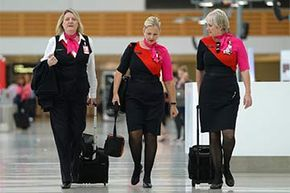 Qantas flight attendants walk through the terminal of the Sydney domestic airport in 2014. The image of flight attendants has changed a lot over the years.
