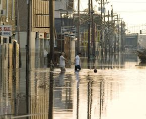 People walking flooded New Orleans streets after the levees broke from the storm surges caused by Hurricane Katrina. See more storm pictures.