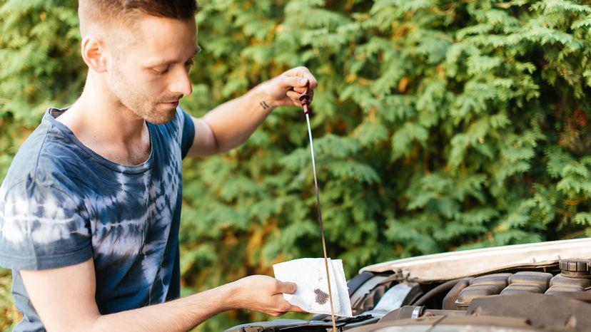 Man checking car oil