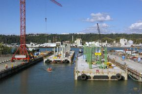 Pontoons are usually put together near the bridge construction site and then towed into place. Here, pontoons float out of the casting basin at Concrete Technology Corporation in Tacoma, Wash. in August 2008.