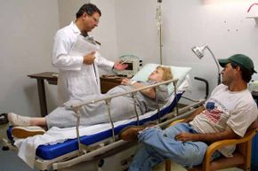 Dr. Robert Hernandez (left) speaks with Connie Adams as she lies in a bed suffering the effects of dehydration resulting from a stomach virus in Louisiana.
