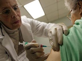 Elaine Louie receives a flu shot, offered free by the city of Chicago, from registered nurse Betty Lewis in October 2006.
