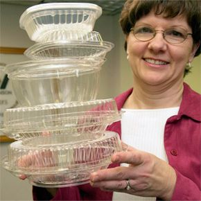 A company employee displays containers made from corn plastics at the Wilkinson Manufacturing Company in Fort Calhoun, Neb.