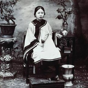 A portrait of young Chinese woman in the 1880s whose tiny feet are the result of the tradition of foot binding.
