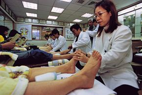 Reflexology therapists treat patients in Taipei, Taiwan. Reflexology could be an effective way to relieve postoperative pain.