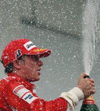 Ferrari driver Kimi Raikkone pops champagne after winning the 2007 World Championship.