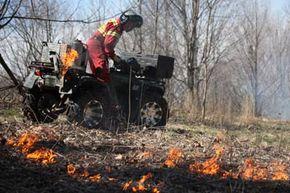 Worker ignites grasslands during a controlled burn