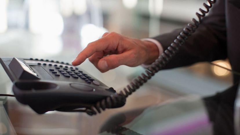 man dialing landline
