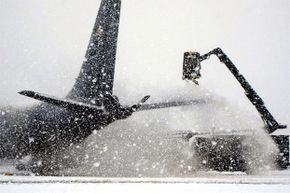A deicer clears snow off a KC-135 Stratotanker before it takes off from Manas Air Base, Kyrgyzstan, bound for Afghanistan.