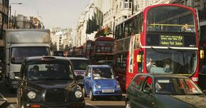The G-Wiz huddles among taxi cabs, delivery trucks and hulking double-decker buses in London, England.
