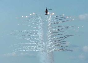 A U.S. Navy helicopter discharges countermeasure flares