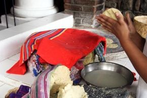 A woman makes tortillas.  Tortillas are staple of the Guatemalan diet.