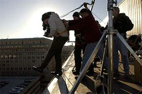 On the location for 'Thank You for Smoking,' director Jason Reitman is held in place by James Whitaker, director of photography, center, and Ted Ayd, gaffer, as he films a scene from atop the Hyatt Regency in Washington, D.C.