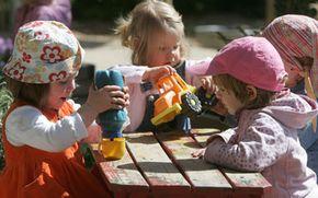 German toddlers play in the garden at the Spreekita kindergarten in Berlin. Kindergarteners' behavior best exemplifies game theory's economic model.