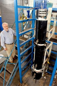The assistant director of Southern Illinois University's Coal Research Center stands next to a model gasification system that separates small amounts of coal into syngas. See more green science pictures.