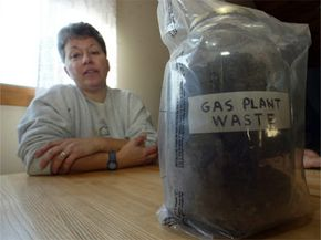 """A Tiverton, R.I., resident poses next to a container labeled """"Gas Plant Waste"""" in 2005. The state believes the area contamination was caused by the Fall River Gas Co. dumping coal gasification waste for decades."""