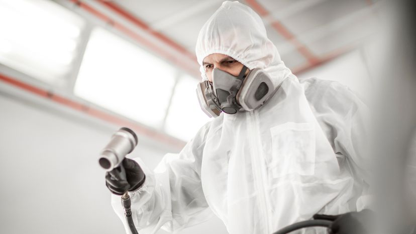 Car painter wearing a gas mask for safety