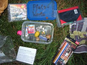 Many geocaches, like this one found in Germany, contain a variety of items, including toys and CDs.