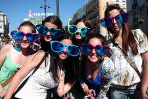 These young Gen Y women live life in the moment while enjoying their vacation in Madrid, Spain. They have fun looking goofy in oversized sunglasses, as long as all their friends look goofy, as well.