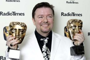 """Actor and writer Ricky Gervais poses holding two awards for """"The Office"""" at the British Academy Television Awards in 2003."""