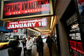 """Pedestrians walk near the marquee of the Broadway show """"Spring Awakening"""" at the Eugene O'Neill Theatre in New York."""