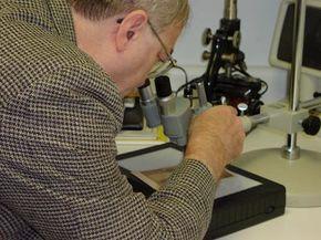 "Paranormal investigator Joe Nickell examines a rare 18th-century ""spirit photograph"" under a stereo microscope."