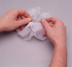 Pull thread ends to gather netting.