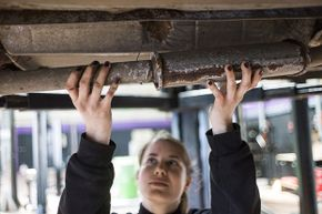 A woman mechanic fixes a car exhaust pipe at an innovative garage and auto repair workshop catering exclusively to female customers in Paris, 2014. Customers can get a massage or manicure while they wait.
