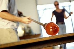 Glassblowers use a number of techniques to shape their glass creations. Here, a glassblower is shaping his piece by rolling it across large flat surface called a marver.