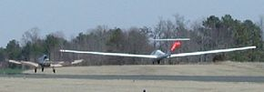 Since the glider's wings generate more lift, it takes off before the tow plane.