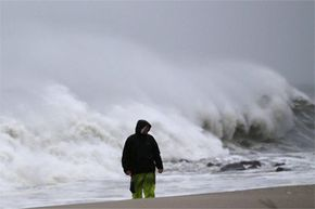In some parts of the U.S. Northeast, Sandy's storm surge was record-breaking. This gentleman is standing on New Jersey's Cape May beach as surf from Sandy thunders onto the shoreline.