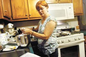 Teresa Andrasik, who organized a support group at St. Mary's Hospital to help others who have celiac disease, checks her recipe as she makes gluten-free cinnamon rolls. Only 1 percent of Americans have celiac disease.