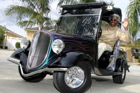 Lillie Lipscomb waves as she drives her golf cart, a fiberglass replica of a 1934 Ford, from her driveway in The Villages, Fla.